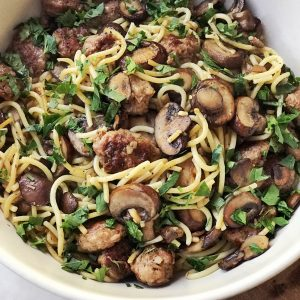 Spaghetti with mushrooms and sausage in a white bowl