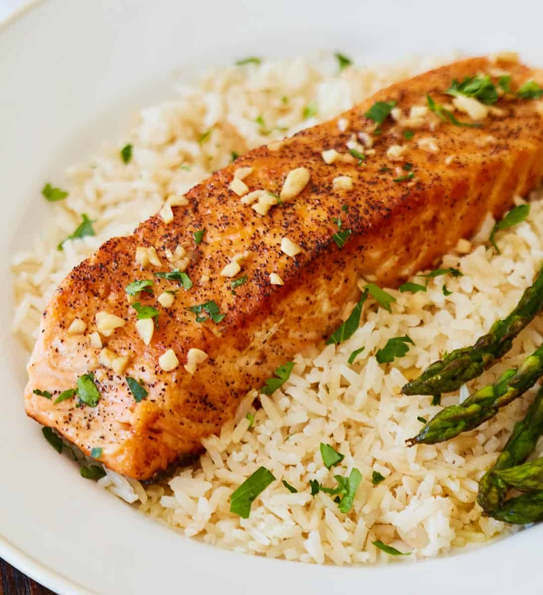 Skillet Salmon in Lemon Butter over bed of brown rice and side of asparagus on white plate