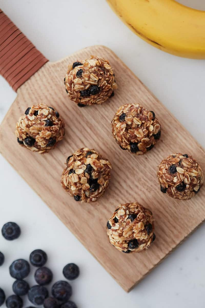 Oatmeal Blueberry Energy Balls on a wooden cutting board