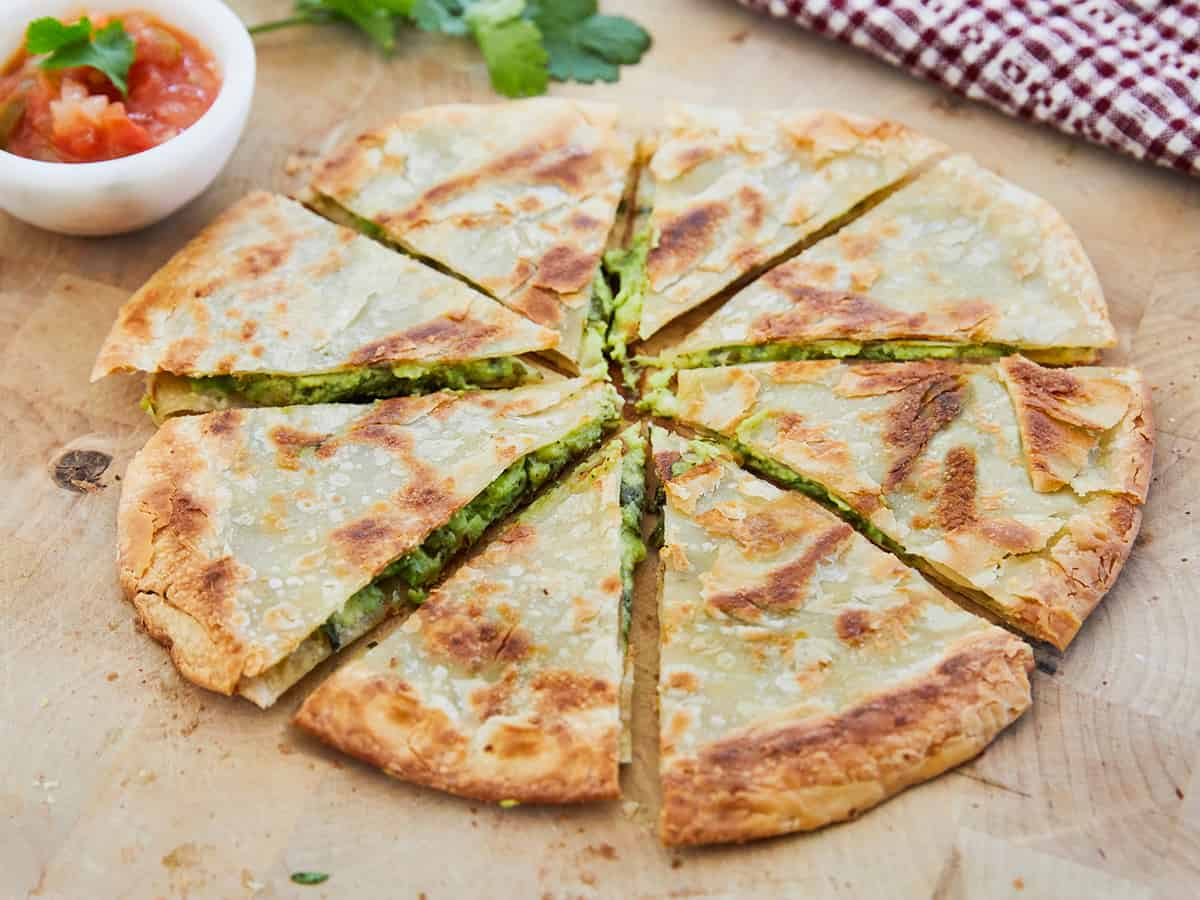 Green Goddess Quesadilla sliced with a side of salsa on wooden surface