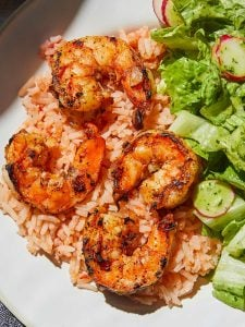 Mexican Style Shrimp and Rice served with a side salad on white plate
