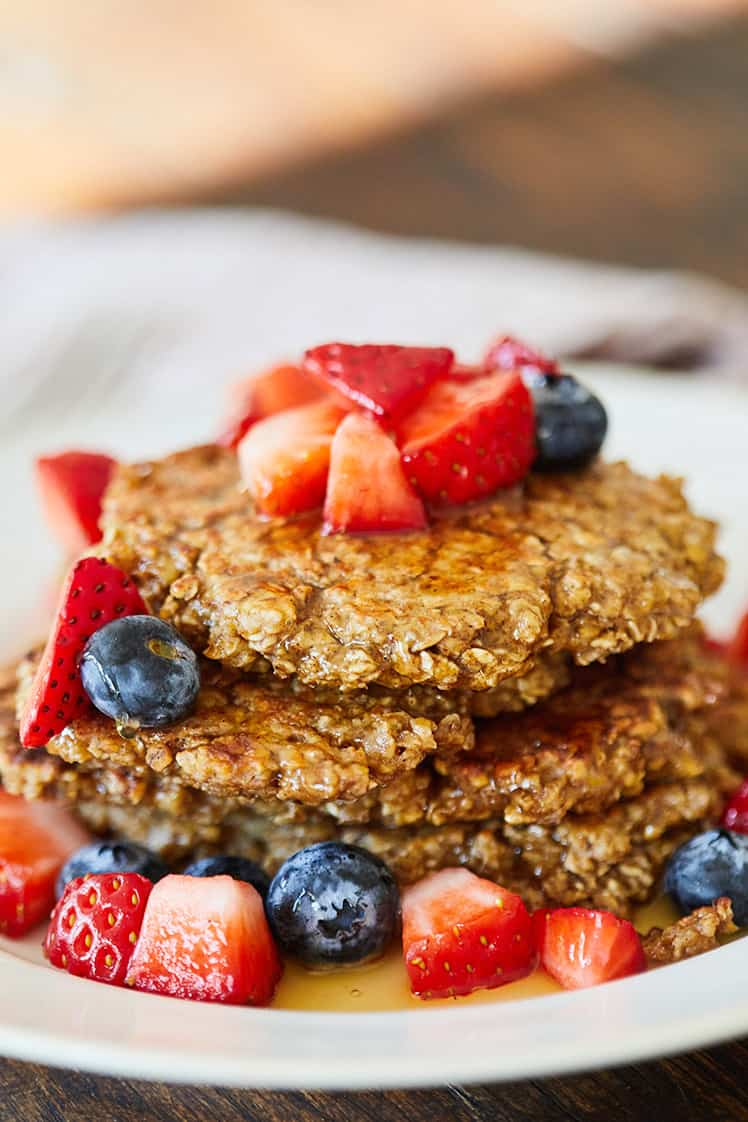 Oatmeal Banana Pancakes topped with fresh strawberries and blueberries on white plate