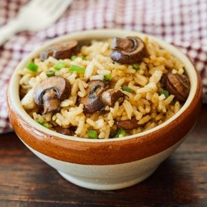 Spicy Mushroom Rice served in a brown bowl next to checkered napkin