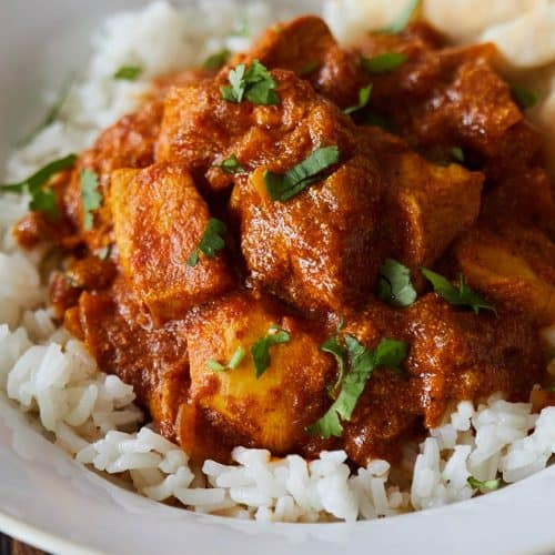Chicken Tikka Masala served over white rice in white bowl