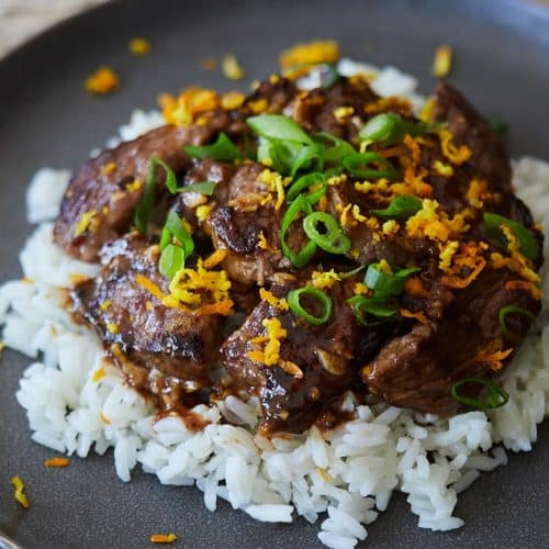 Skillet Orange Beef served over white rice on a gray plate