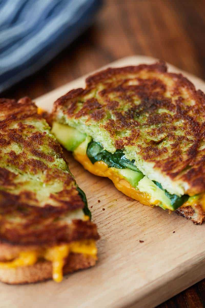 Avocado Pesto Grilled Cheese cut in half on wooden cutting board
