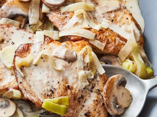Creamy Chicken with Leeks and Mushrooms on a gray plate with serving spoon