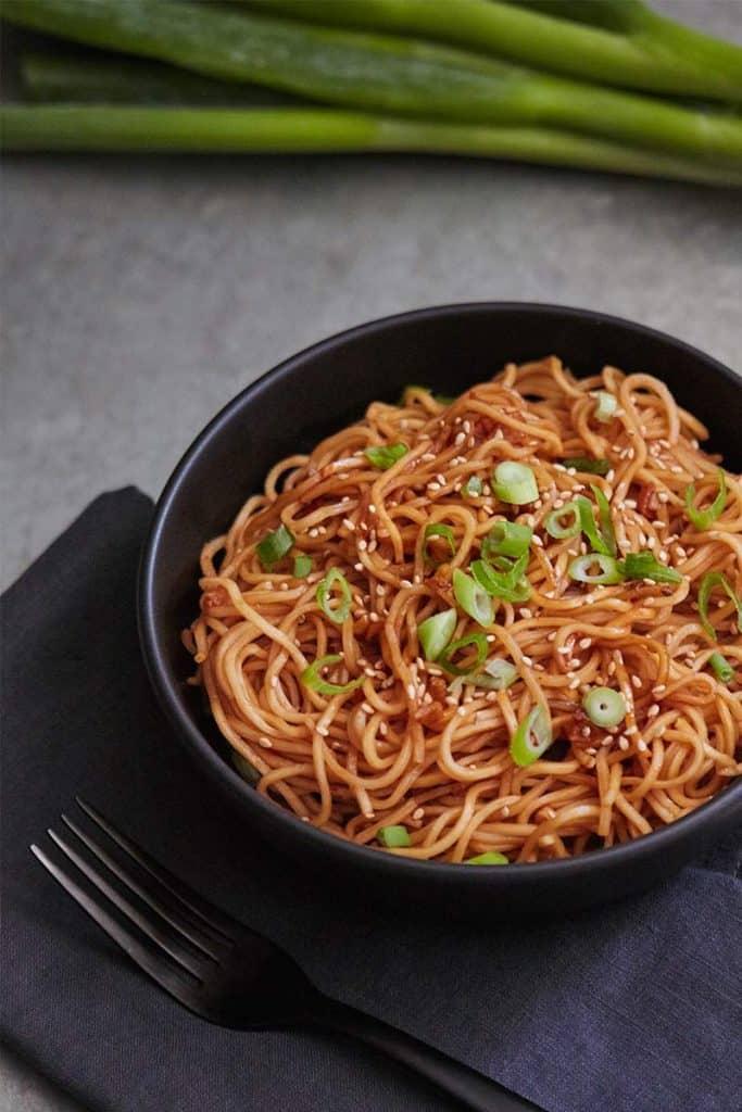 Spicy Sesame Garlic Ramen Noodles served in black bowl next to black napkin on metal surface