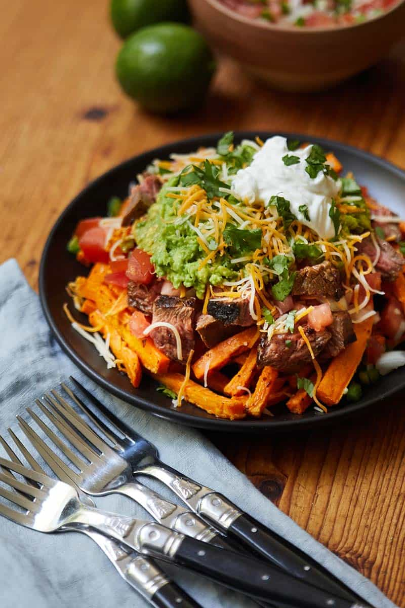 Carne Asada Sweet Potato Fries served on a black plate next to pile of forks