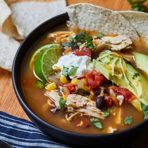 Instant Pot Tortilla Soup with Chicken served in black bowl garnished with tortilla chips