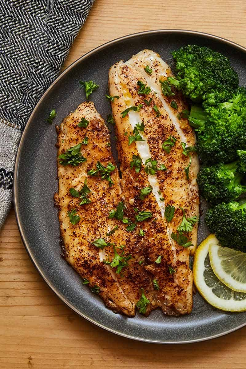 Spicy Lemon Garlic Tilapia served with a side of broccoli on a gray plate
