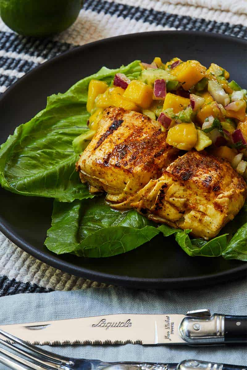 Grilled Halibut with Mango Salsa served on bed of greens on black plate