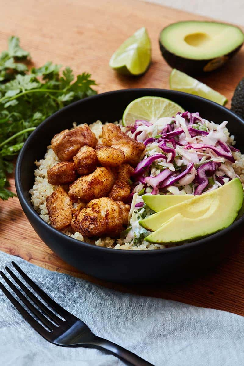 Fish Taco Bowl served in black bowl on wooden surface