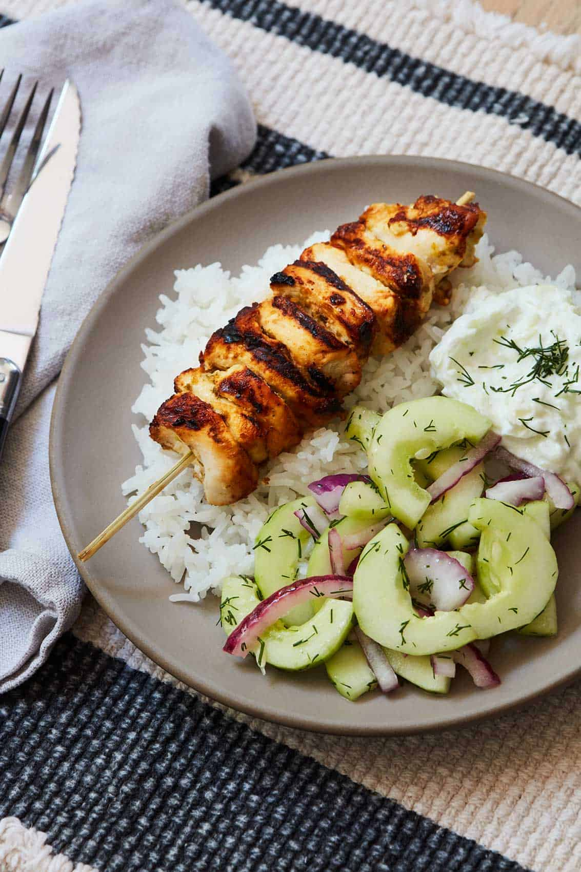 Chicken Skewers with Cucumber Salad and Tzatziki served on a gray plate