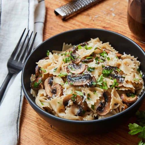 Mushroom Garlic Pasta in a black bowl on wooden surface