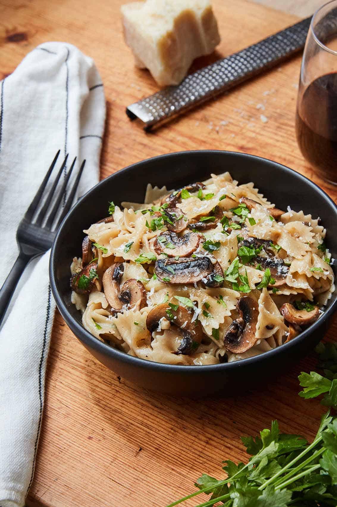 Mushroom Garlic Pasta in a black bowl on wooden surface