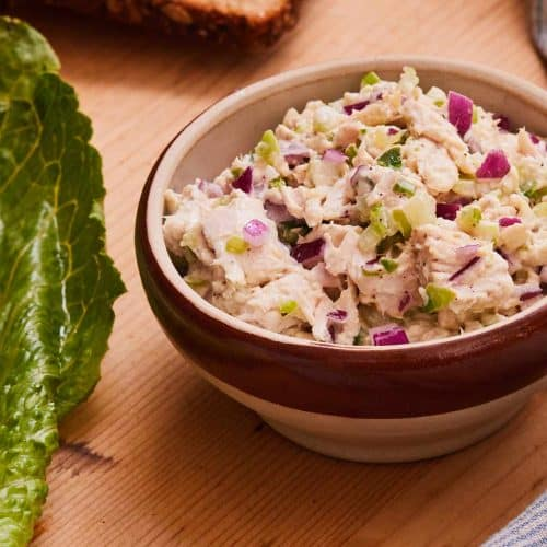 Healthy Chicken Salad in a bowl next to slice of bread and lettuce on a wooden surface