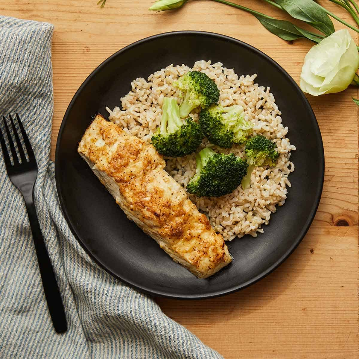 Roasted Dijon Halibut served with brown rice and broccoli on a black plate