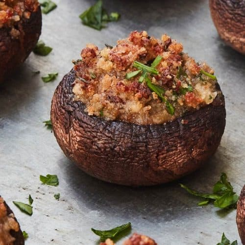 Stuffed Mushrooms garnished with chopped parsley on metal surface