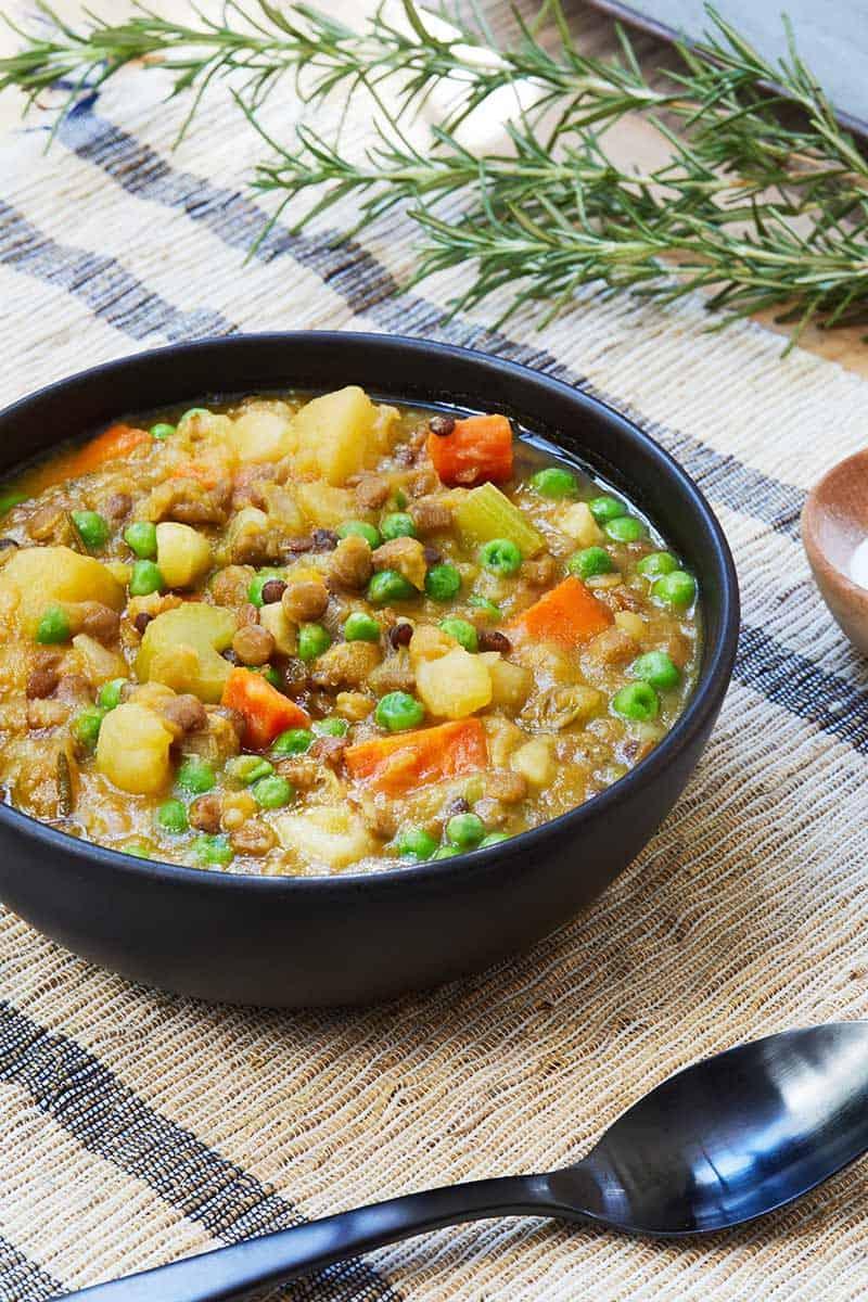 Vegan Lentil Stew served in black bowl on placemat
