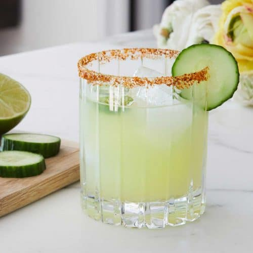 Skinny Spicy Cucumber Margarita served in a glass with cucumber wedge garnish on a marble countertop