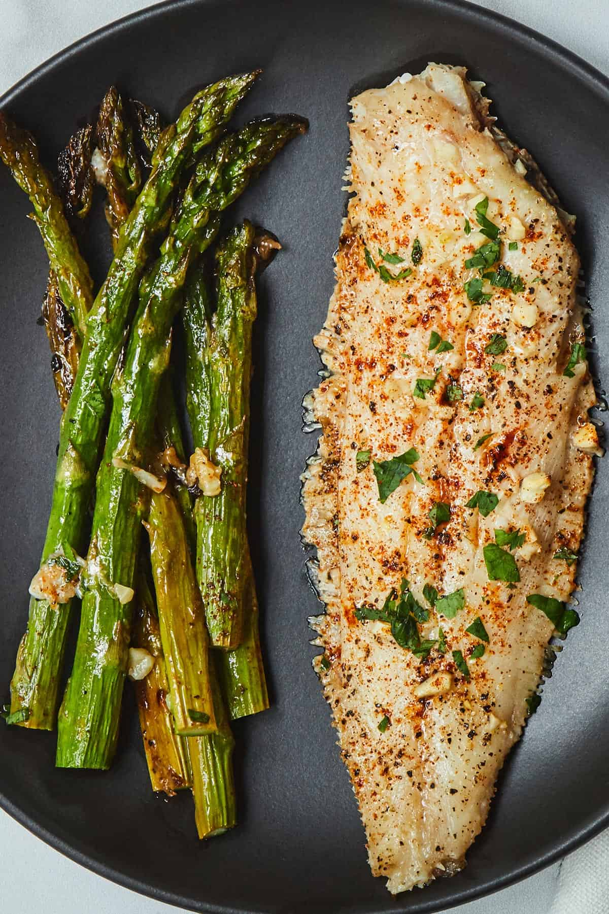 Sheet Pan Garlic Butter Sole with a side of asparagus on a black plate