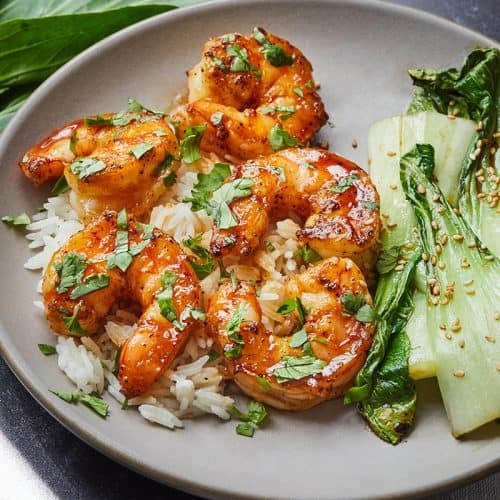 Sweet and Spicy Shrimp served over rice and a side of bok choy on a gray plate