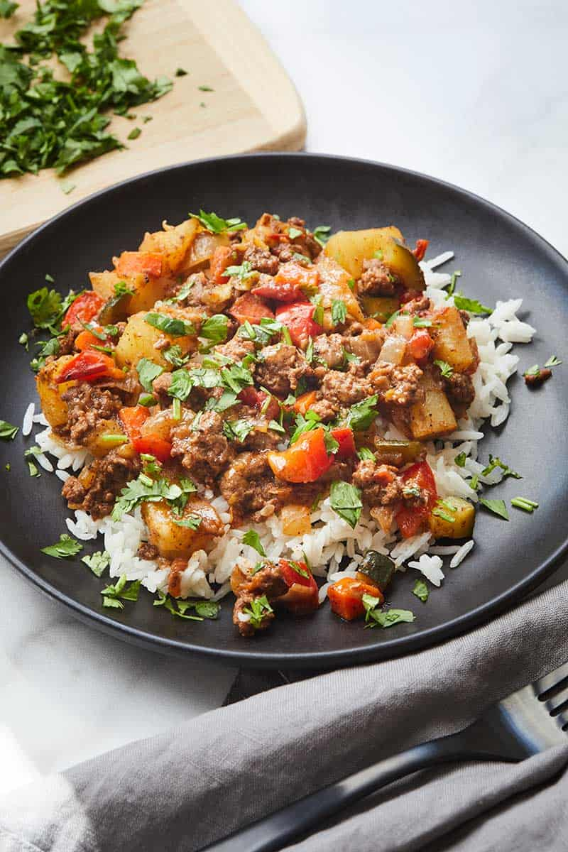 Easy Mexican Picadillo served over rice on a black plate