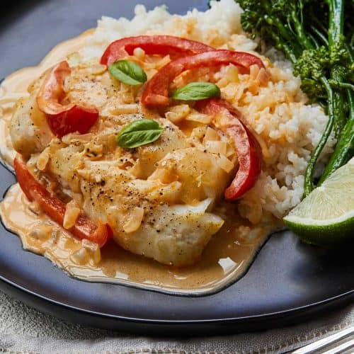 Easy Thai Fish Curry with Broccolini on a black plate garnished with a lime wedge