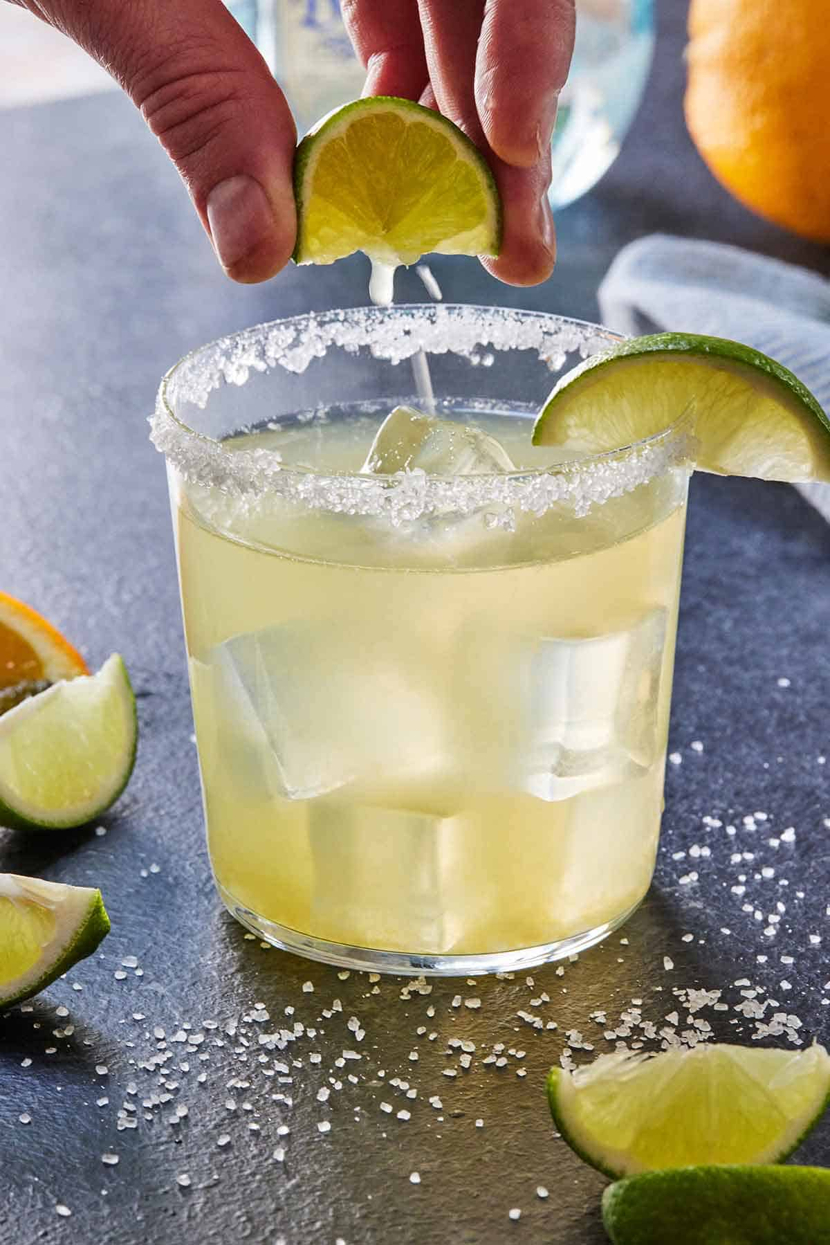 A glass of skinny margarita with a lime wedge being squeezed overtop.