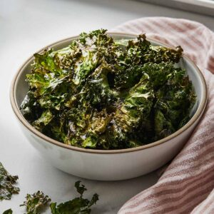 Kale chips in a bowl beside a pink and white linen.