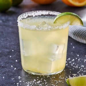 Skinny margarita with a lime wedge on the salted rim.