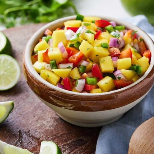 Mango salsa in a bowl beside lime wedges and mango.
