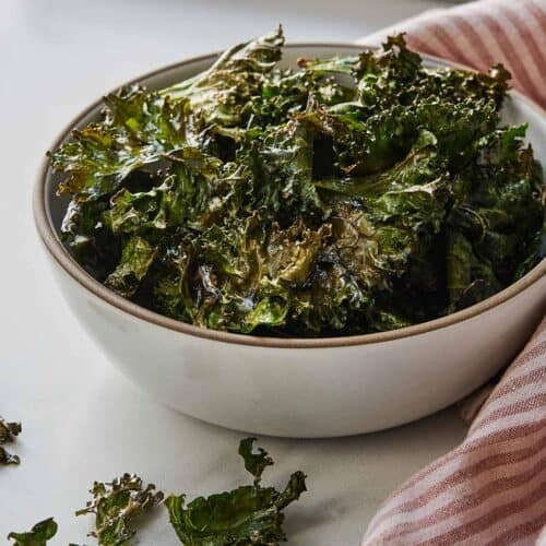 A bowl of crispy kale chips beside a pink and white linen.