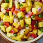 Pinterest graphic of a close up of mango salsa in a bowl.