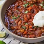Pinterest graphic of a bowl of vegetarian chili with a spoonful of sour cream on top.