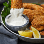 Pinterest graphic of an air fryer chicken tender being dipped into a sauce.