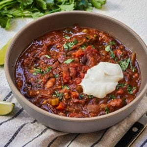 Bowl of chili with sour cream on top.