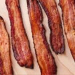 Pinterest graphic of bacon made in the air fryer laying on the cutting board.
