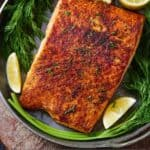 Pinterest graphic of overhead view of a plate of salmon with garnishes.