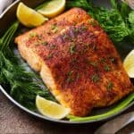 Pinterest graphic of a serving plate of salmon with garnish and lemon.
