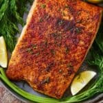 Pinterest graphic of a salmon fillet in a bowl beside herbs and lemon wedges.