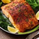 Pinterest graphic of a plate of salmon garnished with herbs and lemon wedges.