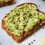 Pinterest graphic of a slice of avocado toast with red chili flakes overtop.