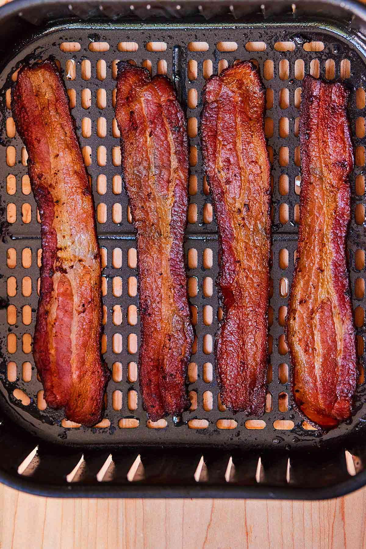 Four slices of bacon in an air fryer basket.