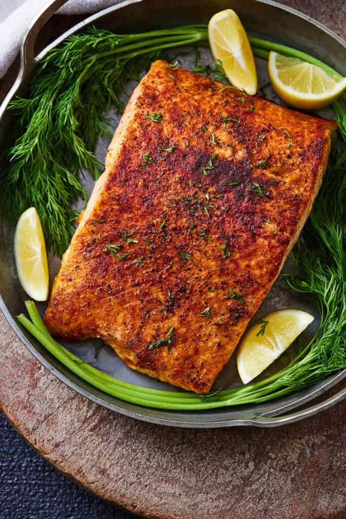 Air fryer salmon with lemon wedges and greens in a serving platter.