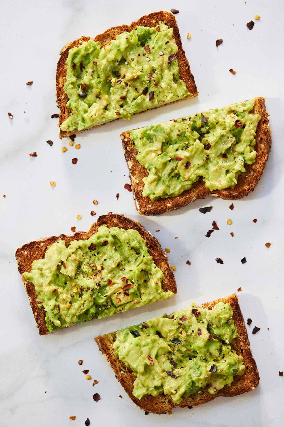 Two slices of avocado toast, each cut in half.
