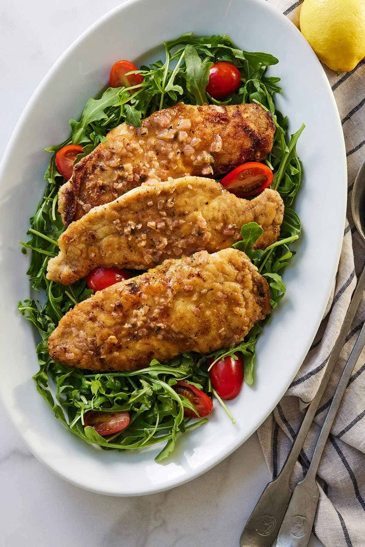 A platter of three chicken paillard overtop of a bed of arugula and cherry tomatoes.