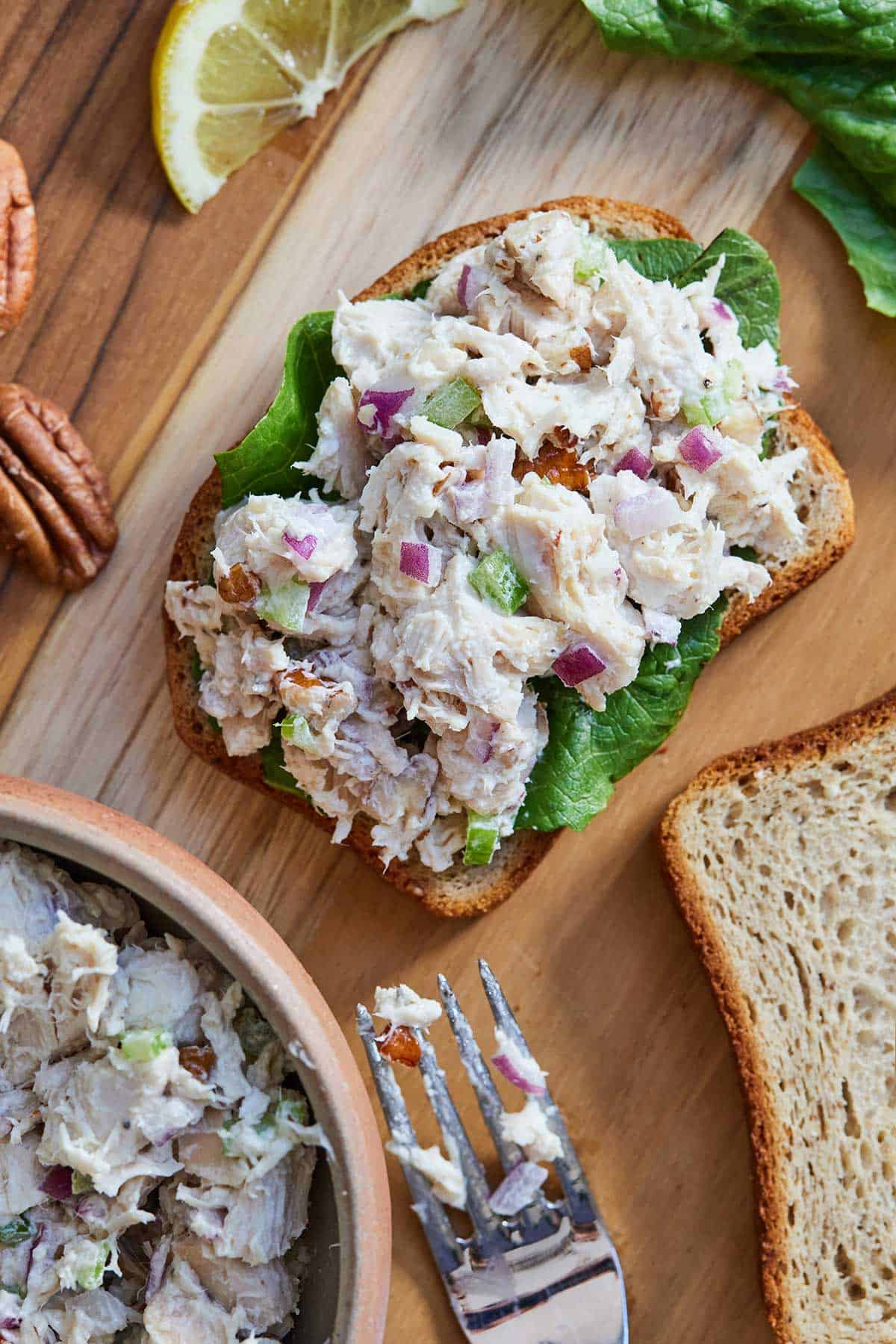 Chicken salad on top of a piece of toast with lettuce in-between with a bowl, bread, lemon wedge, and pecans beside it.