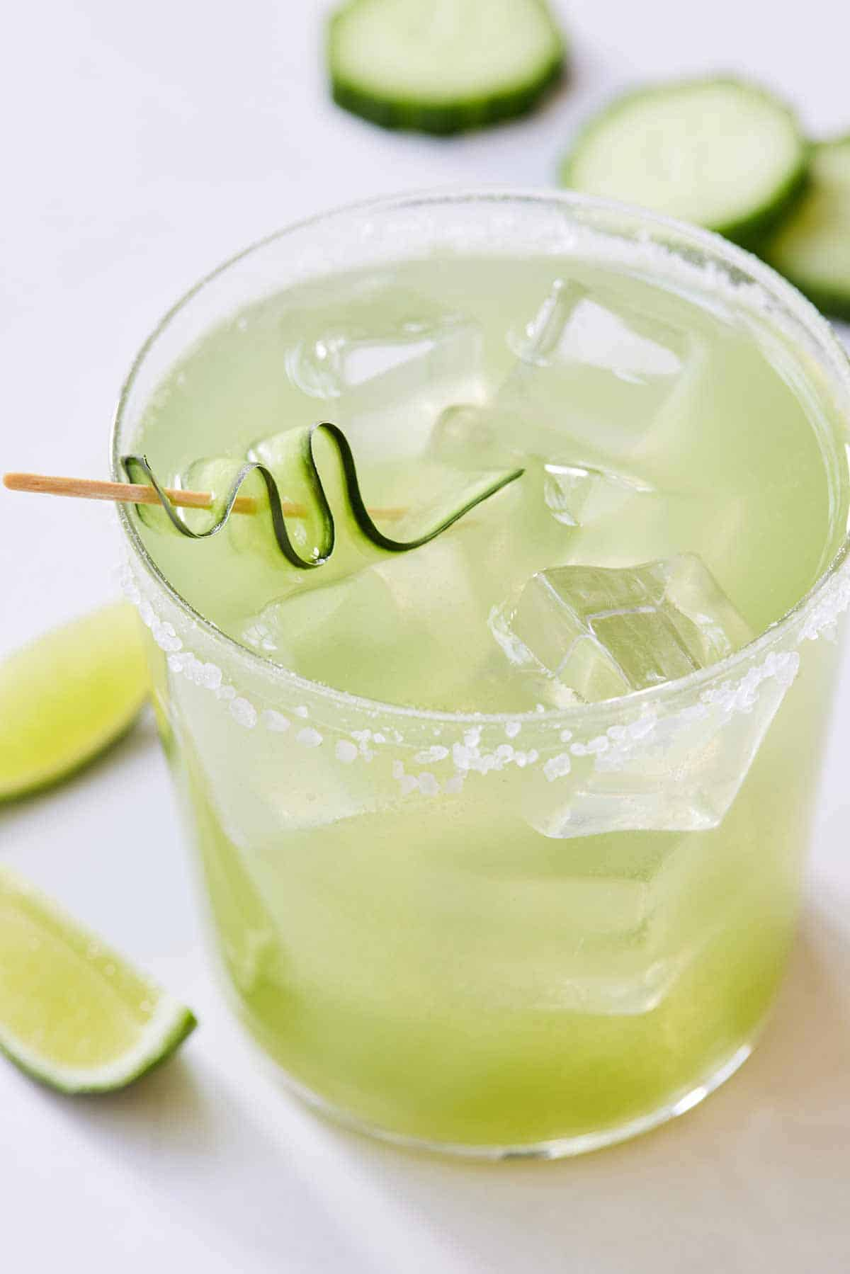 Close up of a glass of cucumber margarita with a cucumber ribbon in a toothpick as garnish.